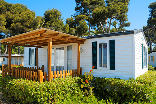 Mobile Home with bushes and trees